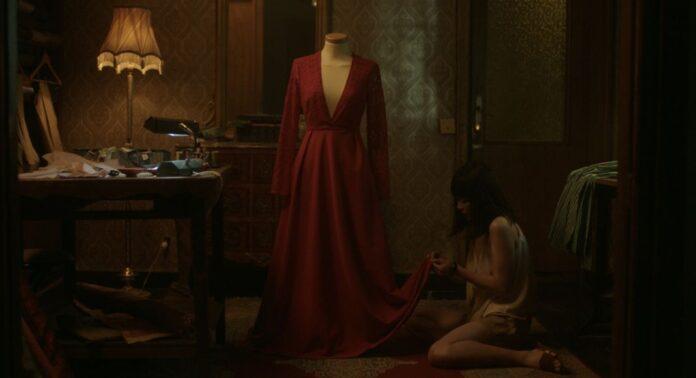 Fotograma del corto 'Xian Xiao', Una mujer cose del dobladillo de un vestido rojo colgado en un maniquí