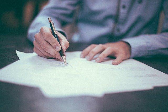 Unas manos con una pluma escribiendo sobre unos papeles