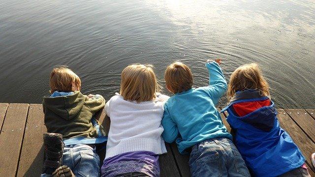 Cuatro niños juganod al borde de un estanque