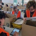 Un grupo de tres personas de Voluntarios por Madrid escrutando el voto por correo con una tablet.
