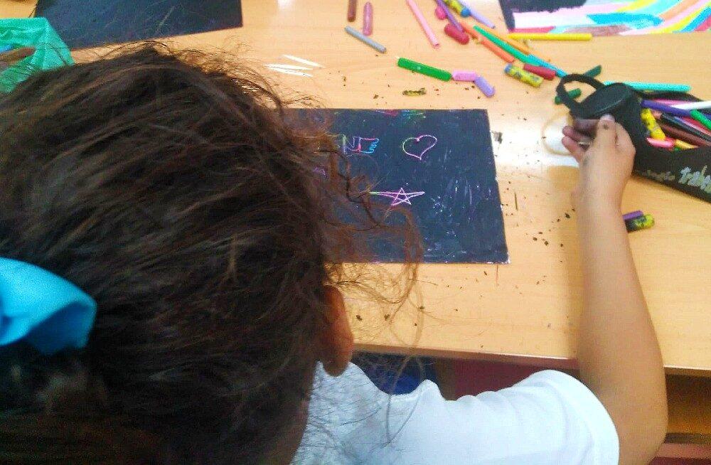 Niña jugando con pinturas en ludoteca de Latina
