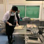 Preparando pescado en las cocinas solidarias de Latina
