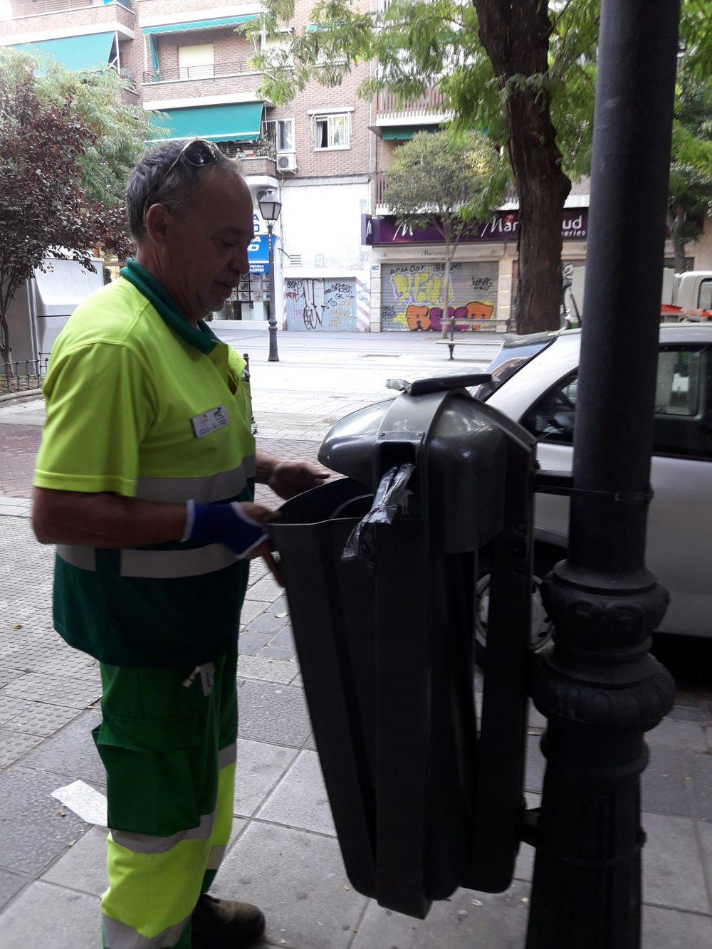 Empleado de limpieza revisando mobiliario urbano