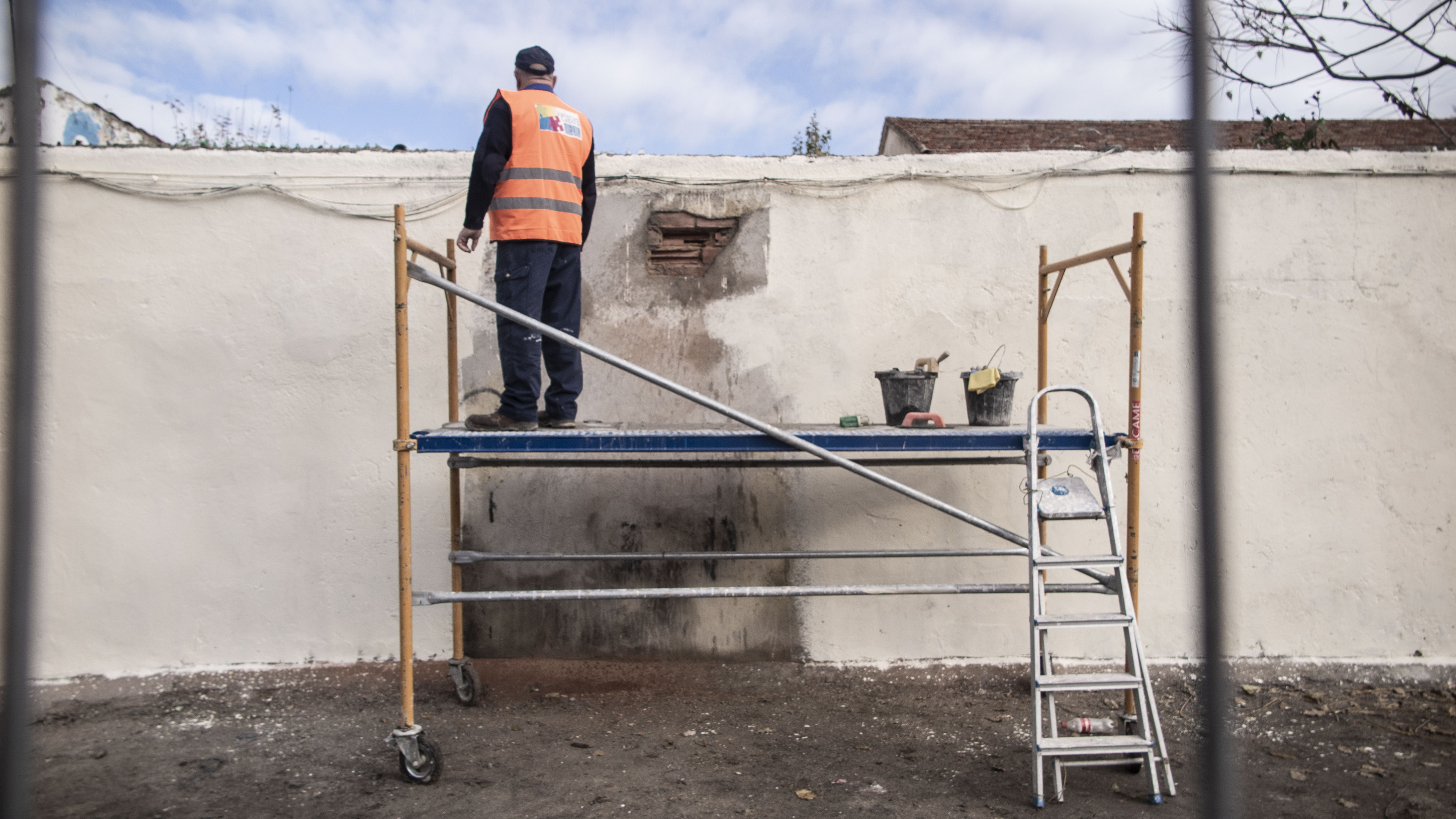 Los miembros de Vallecas Labora reparan la pared en la que se instalará el mural conmemorativo