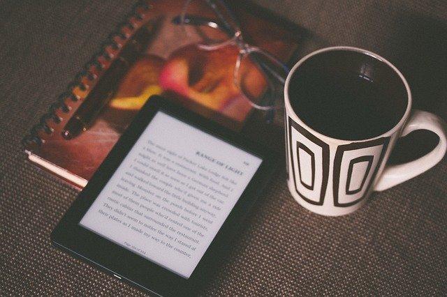 lector electrónico, taza, libreta y gafas
