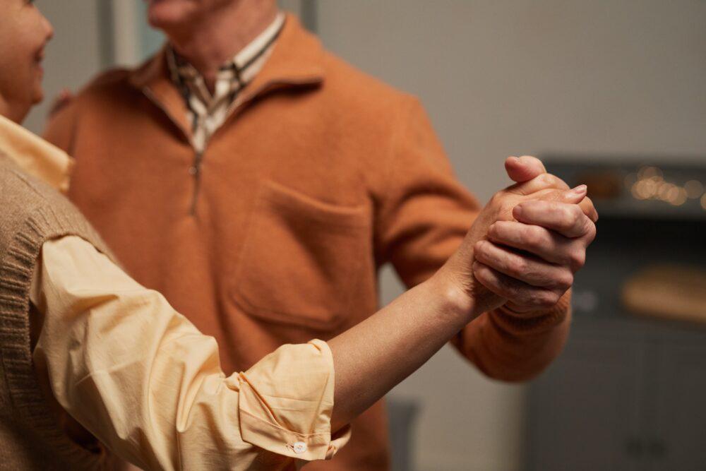 Detalle del torso y bracos de dos personas mayores bailando