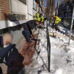 Despejando la nieve de acera y escaleras en la calle Villacarlos