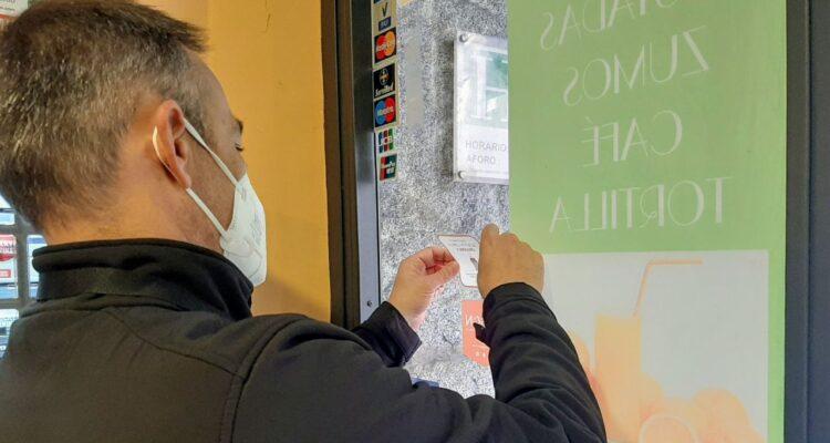 Comerciante colocando el adhesivo con el que reconoce que él sí acierta con la orgánica
