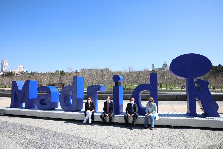 Maíllo, Almeida, Carabante y Sordo sentados en la escultura Madrid Río